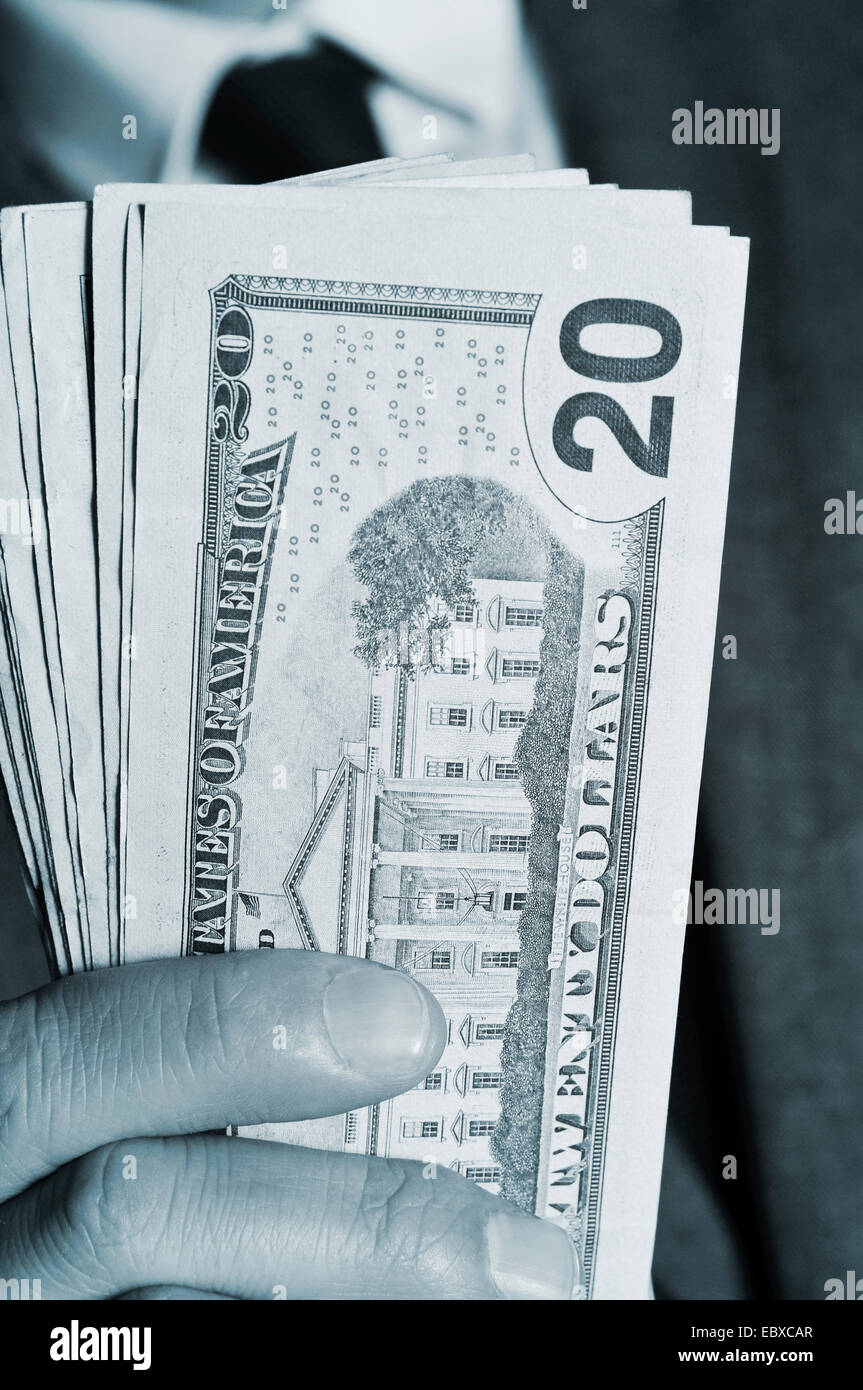 a man wearing a suit showing a wad of dollar bills - Stock Image