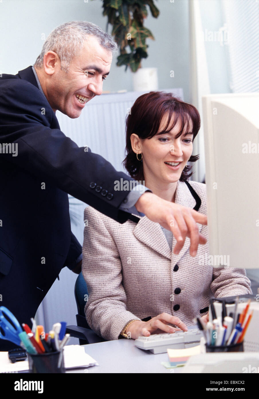 secretary and chief looking together to the PC - Stock Image