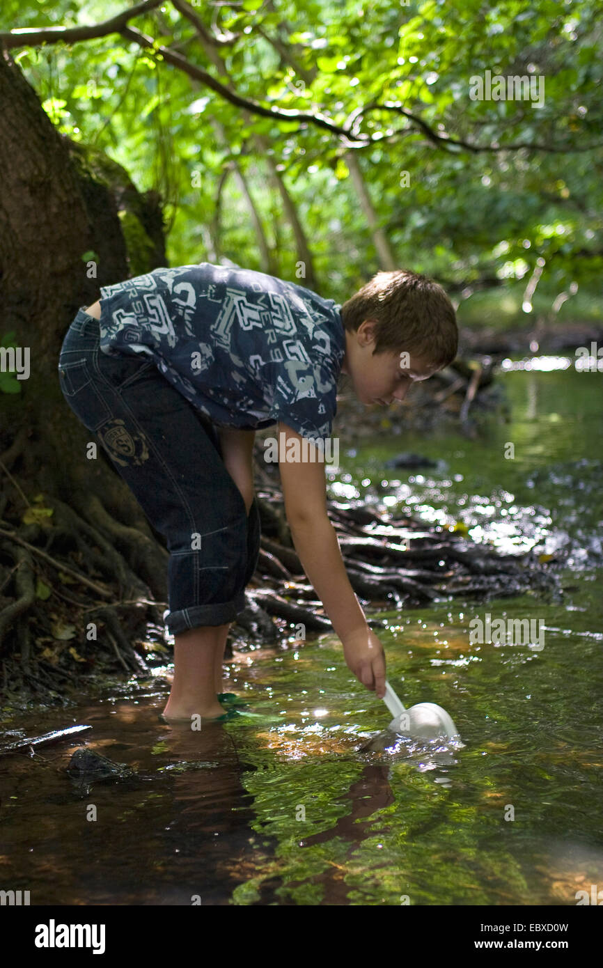 boy with dip net in a creek - Stock Image