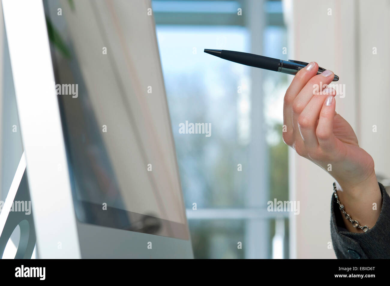 businesswoman points on monitor - Stock Image