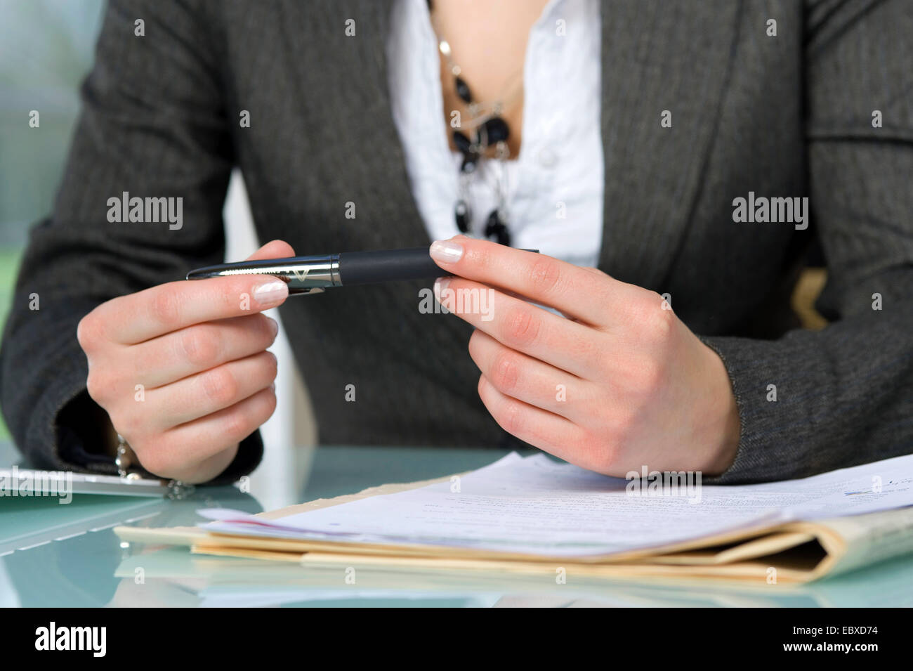 businesswoman with ballpen in hands - Stock Image