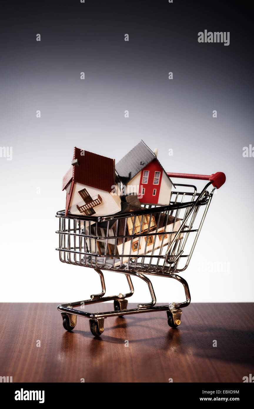 Three models of houses are stacked in a shopping cart. Stock Photo