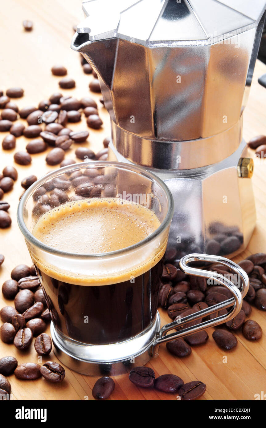 a moka pot and a cup of coffee on a wooden table with roasted coffee beans - Stock Image