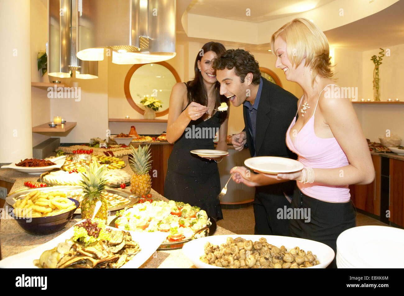 Man and two women serving themselves at a buffet - Stock Image