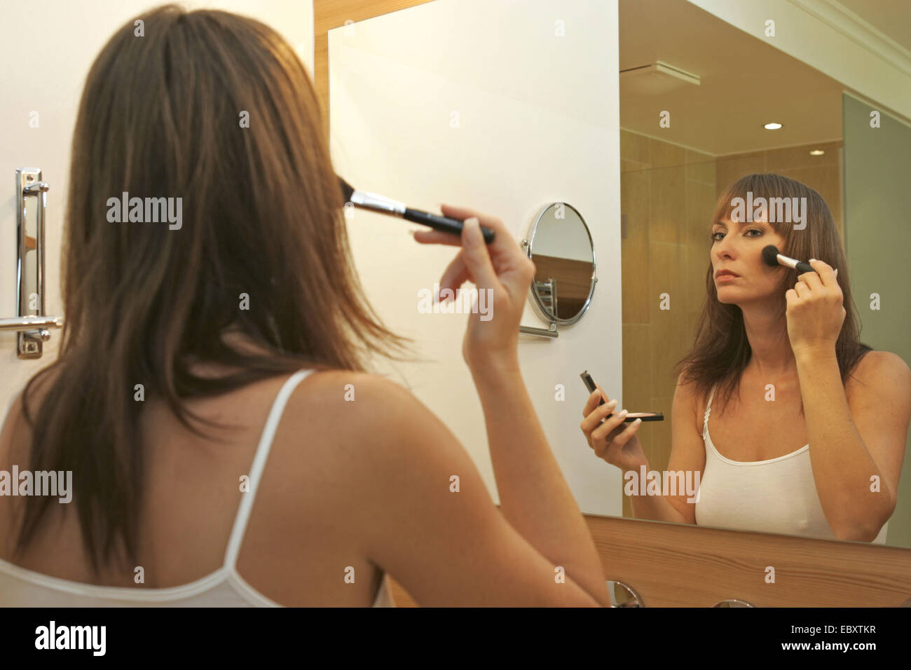 woman putting on make up in bathroom Stock Photo