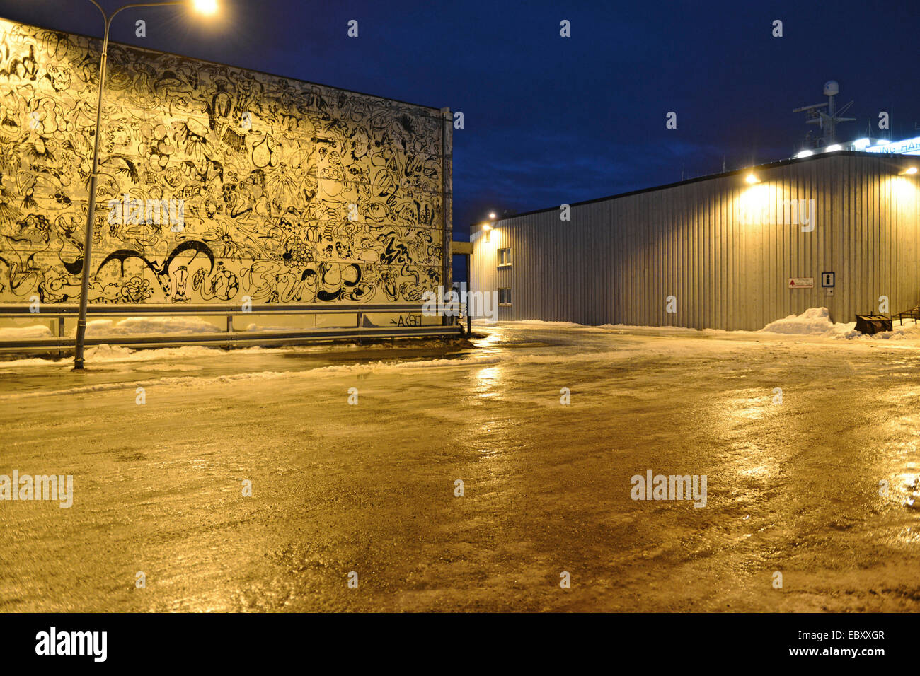 Painted wall of a warehouse illuminated by the street lightning in ...