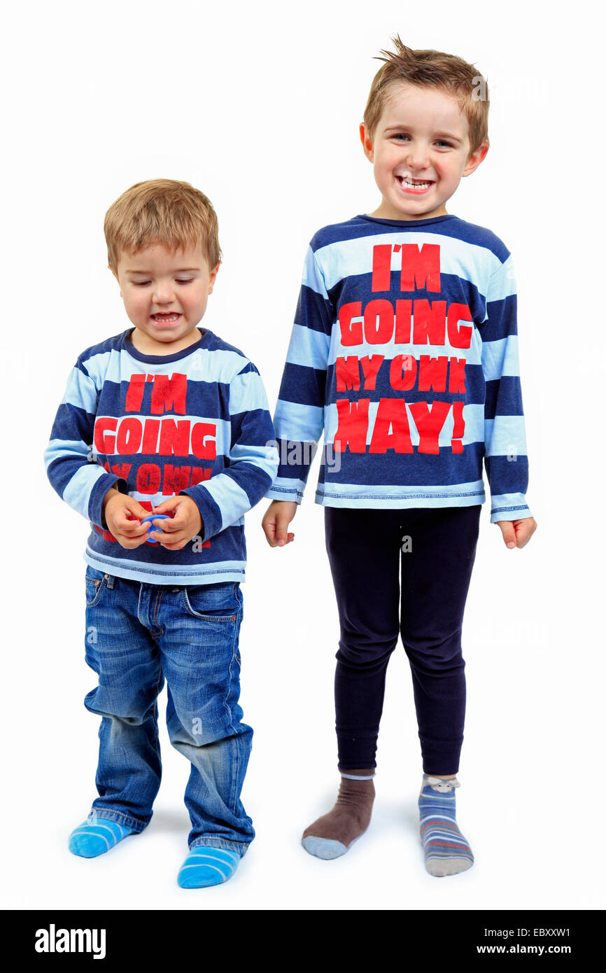 two little boys side by side in striped sweatshirts with the writing 'I'm going my own way!' - Stock Image