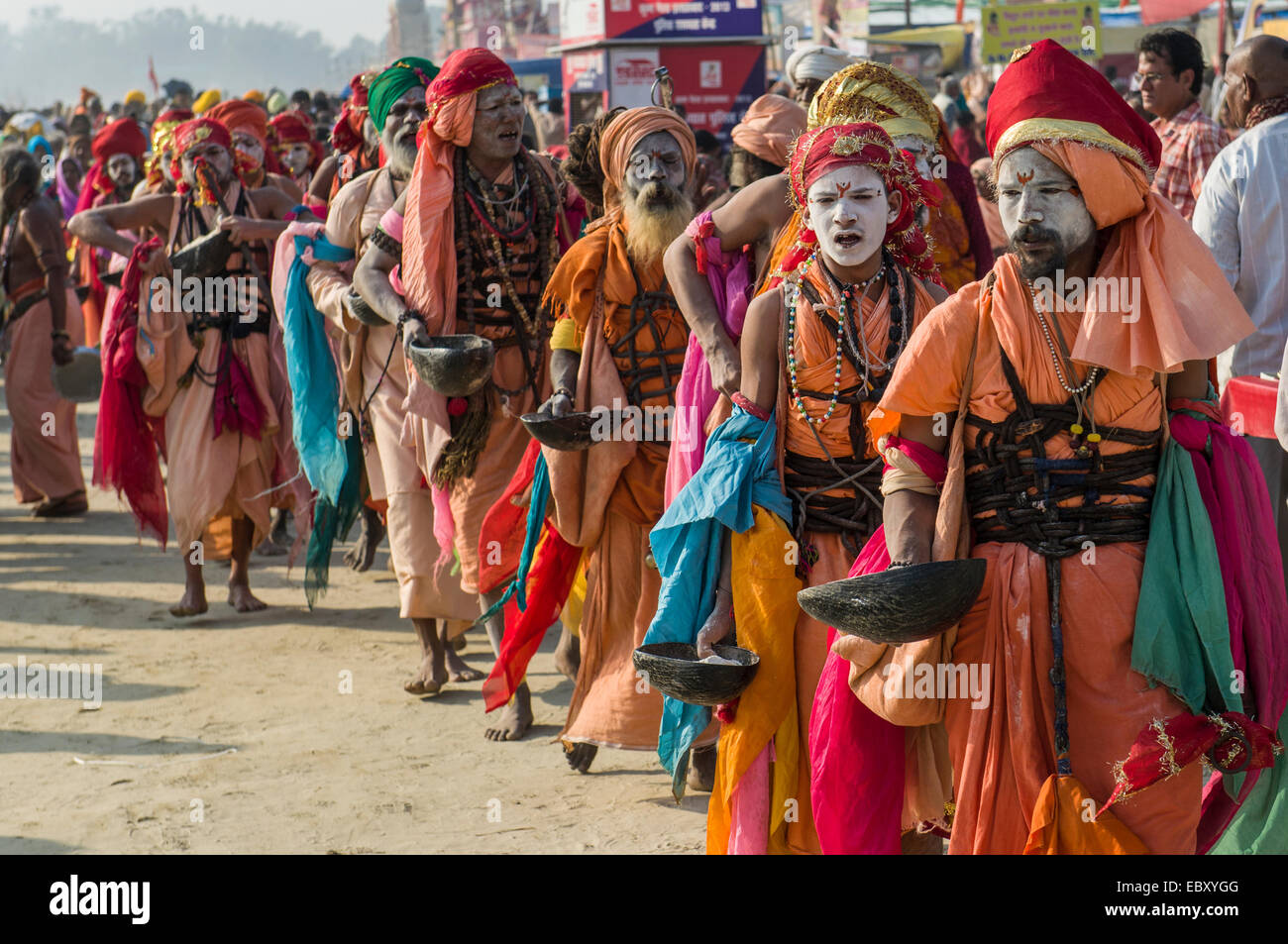 Group of Gudar Sadhus, holy men, walking in a row and collecting offered food from fellow sadhus, at the Sangam, - Stock Image
