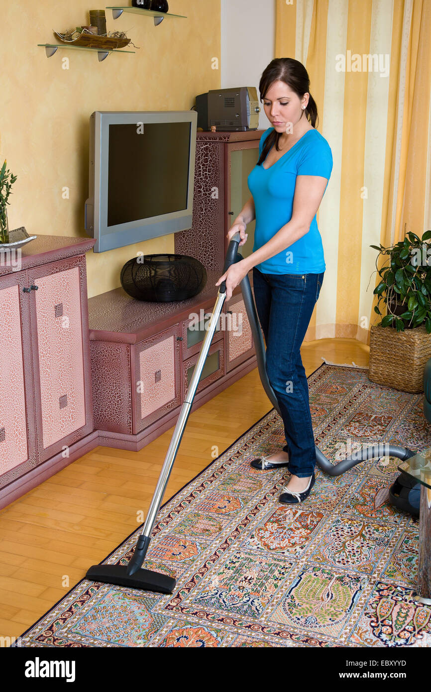 woman using vacuum cleaner - Stock Image