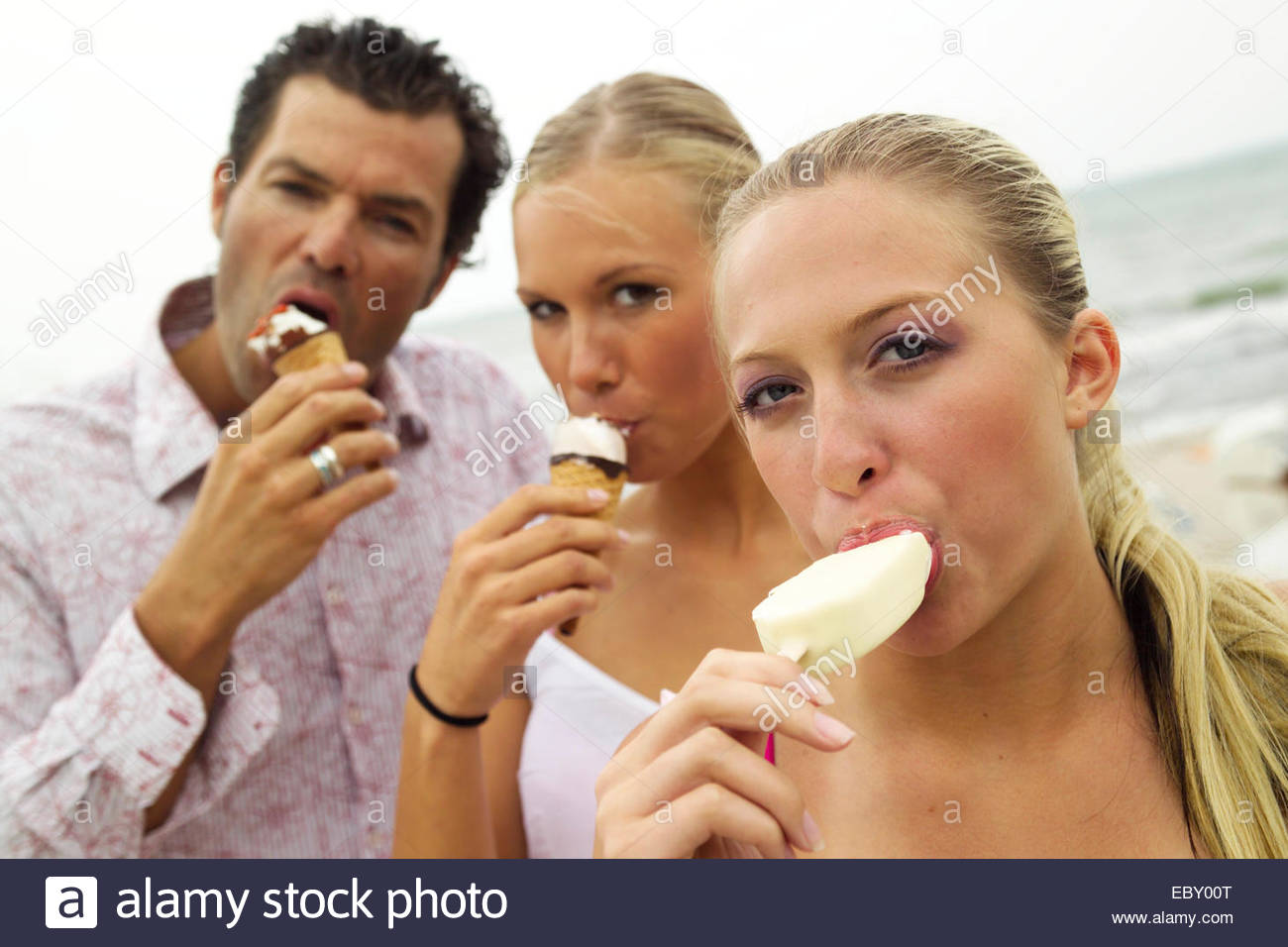man with two blondes eating ice cream - Stock Image