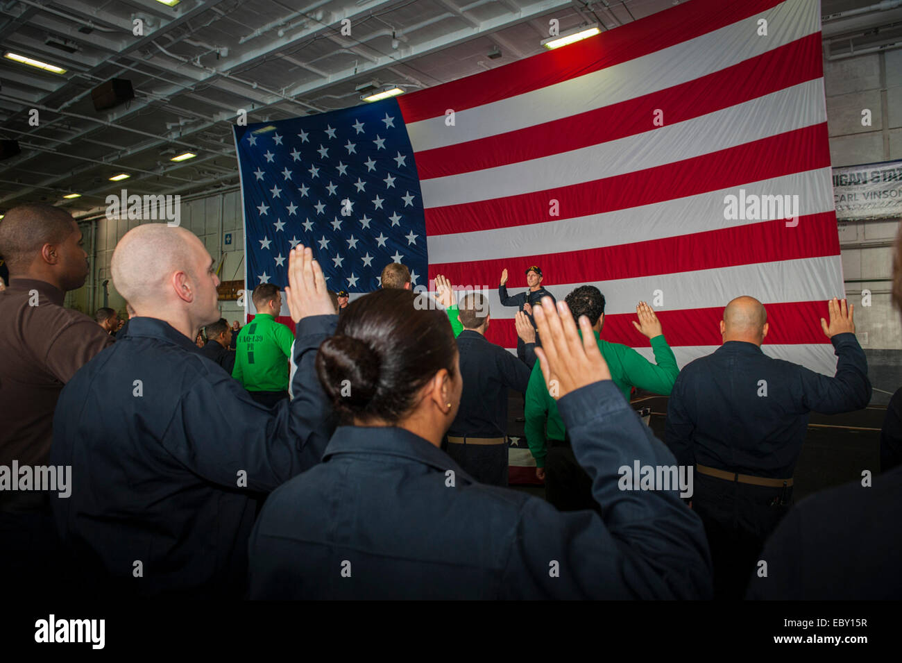 Chief of Naval Operations Adm. Jonathan Greenert re-enlists sailors during an all hands call in the hanger bay aboard - Stock Image