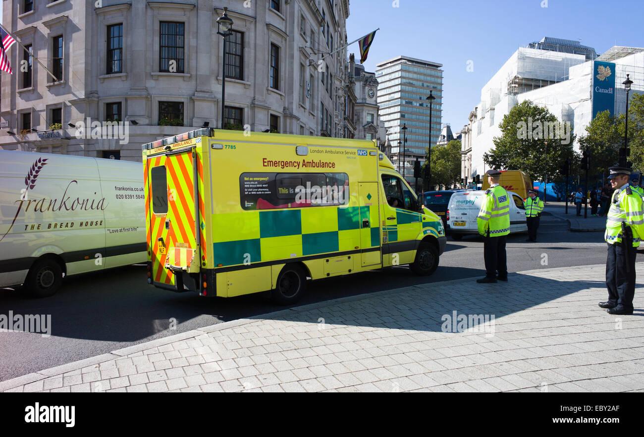 A London ambulance is helped through traffic by Police near Trafalgar square Stock Photo