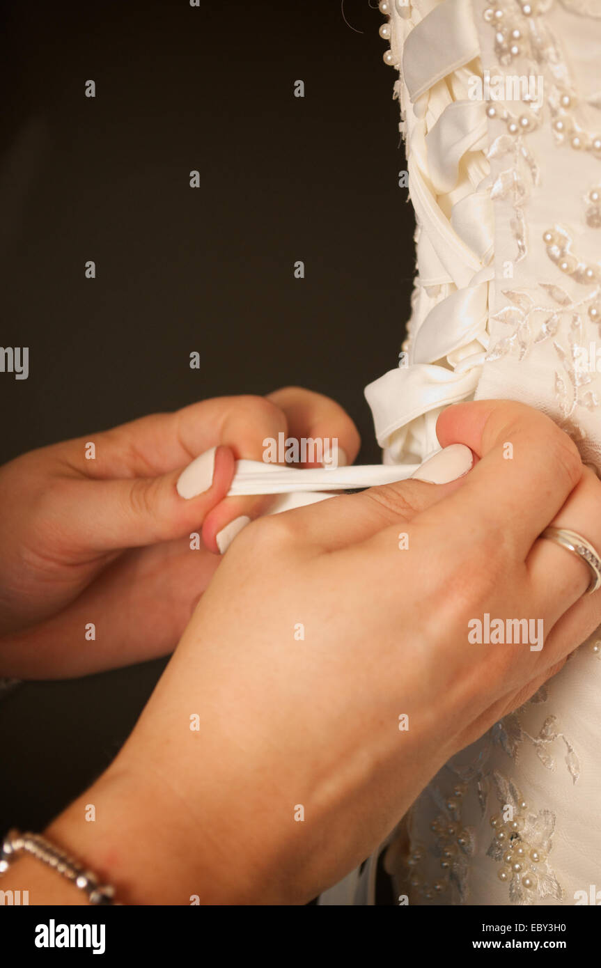 Wedding dress corset being tied from behind. - Stock Image