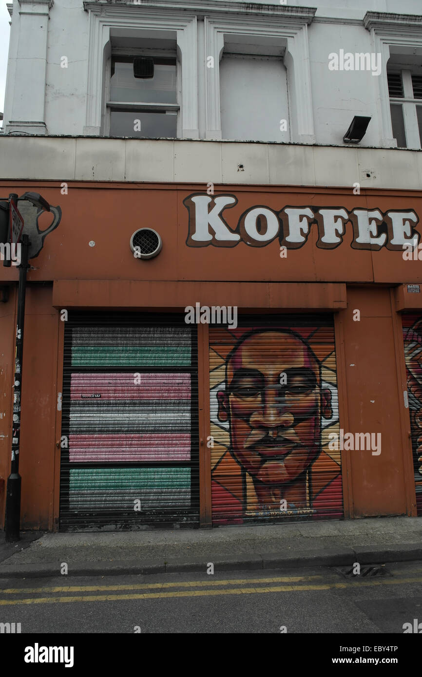 Portrait closed roller blinds Koffee Pot Cafe with coloured bands and British-African man image, Spear Street, Manchester, - Stock Image