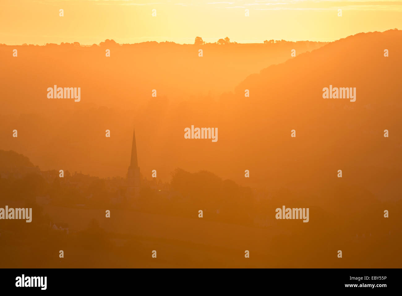 Painswick Church in the Cotswolds at sunrise on a misty morning, Gloucestershire, England. Autumn (September) 2014. - Stock Image