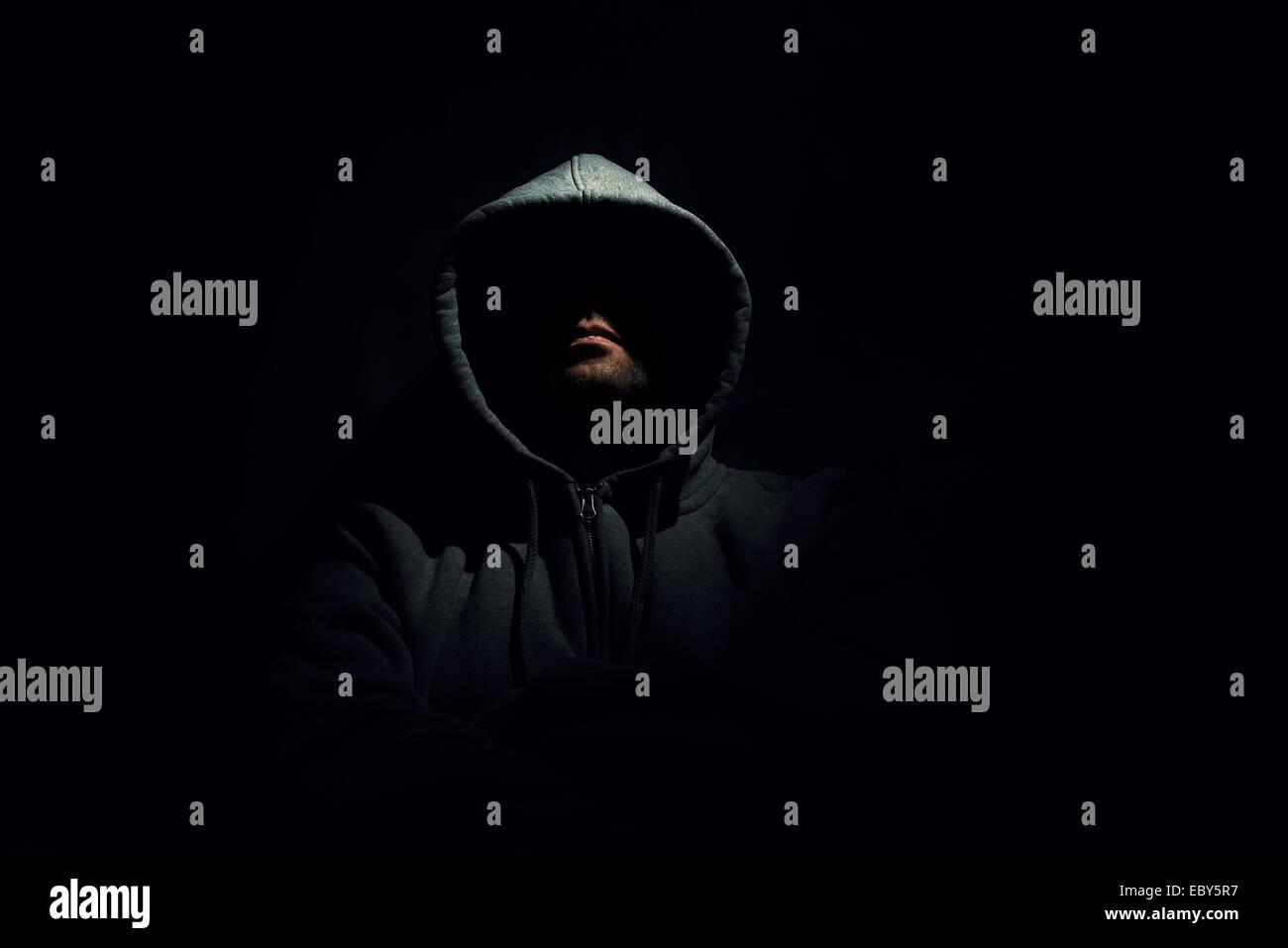 Anonymous man wearing a hoodie sweater in dark surrounding - Stock Image