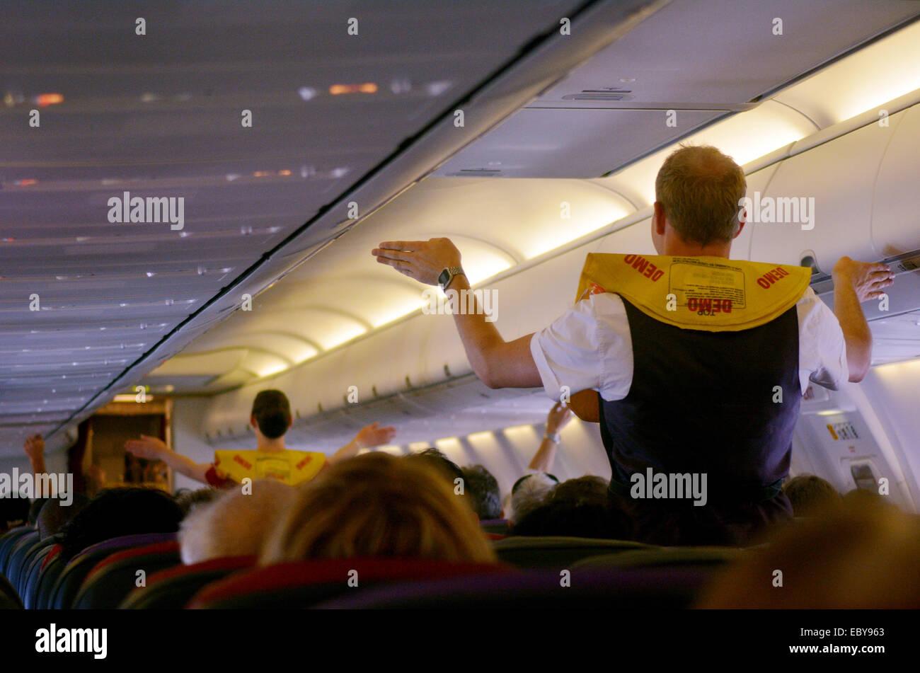 GOLD COAST, AUS - NOV 22 2014:Flight attendants during Pre-flight safety demonstration. If an emergency happens - Stock Image