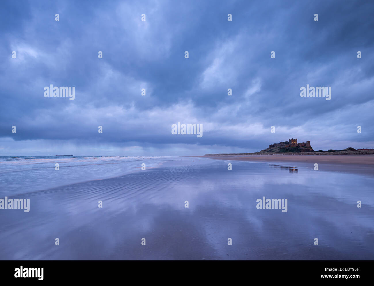 Stormclouds reflect on the deserted beach beside Bamburgh Castle, Northumberland, England. Winter (March) 2014. - Stock Image