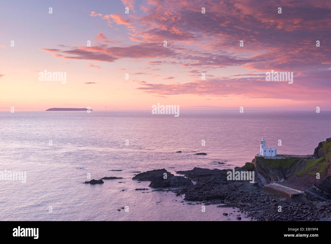 Hartland Point Lighthouse and Lundy Island beneath a colourful sunset, North Devon, England. Spring (May) 2014. - Stock Image