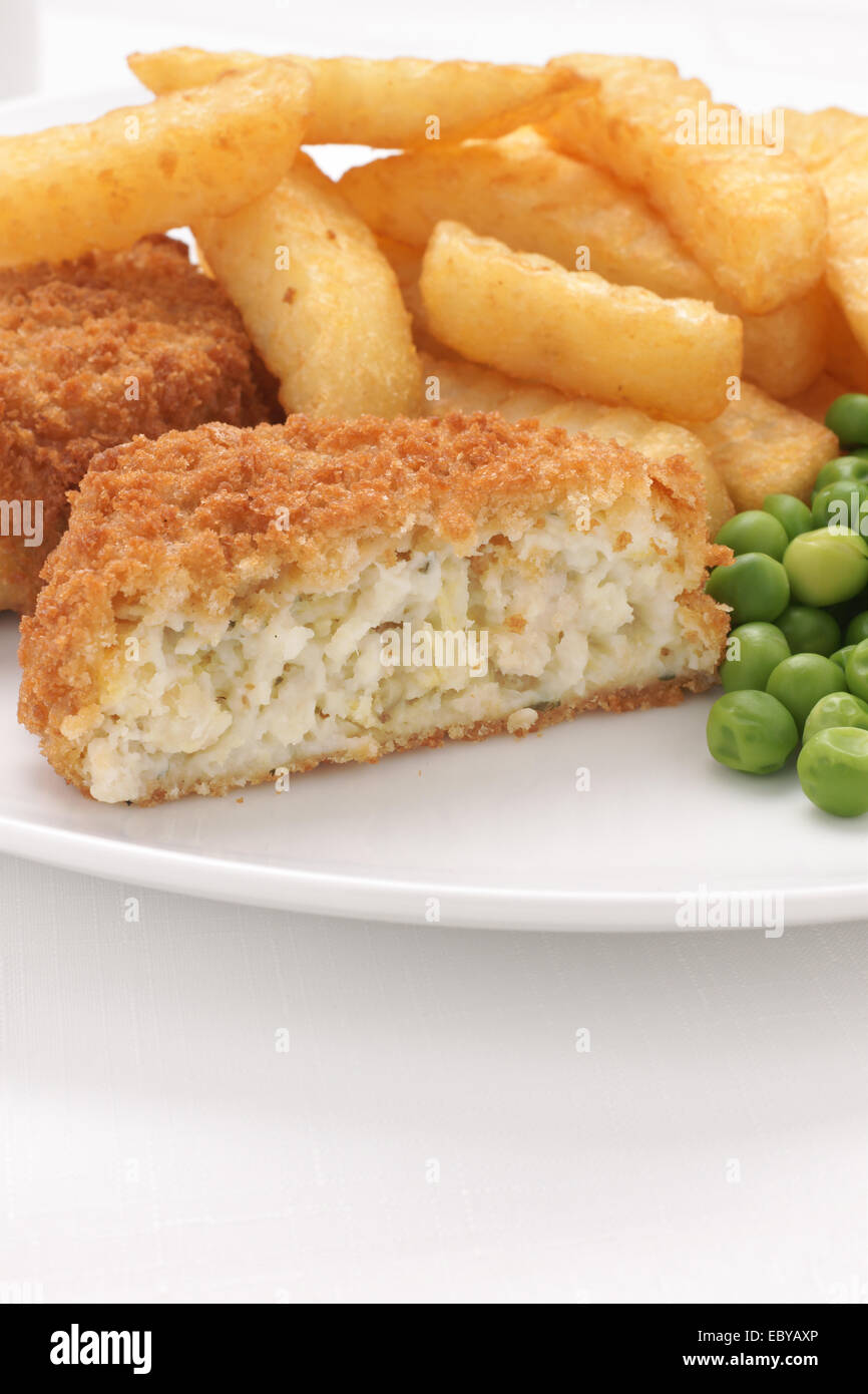 Fishcake made with crumbed fish and potato served with chips and peas - Stock Image