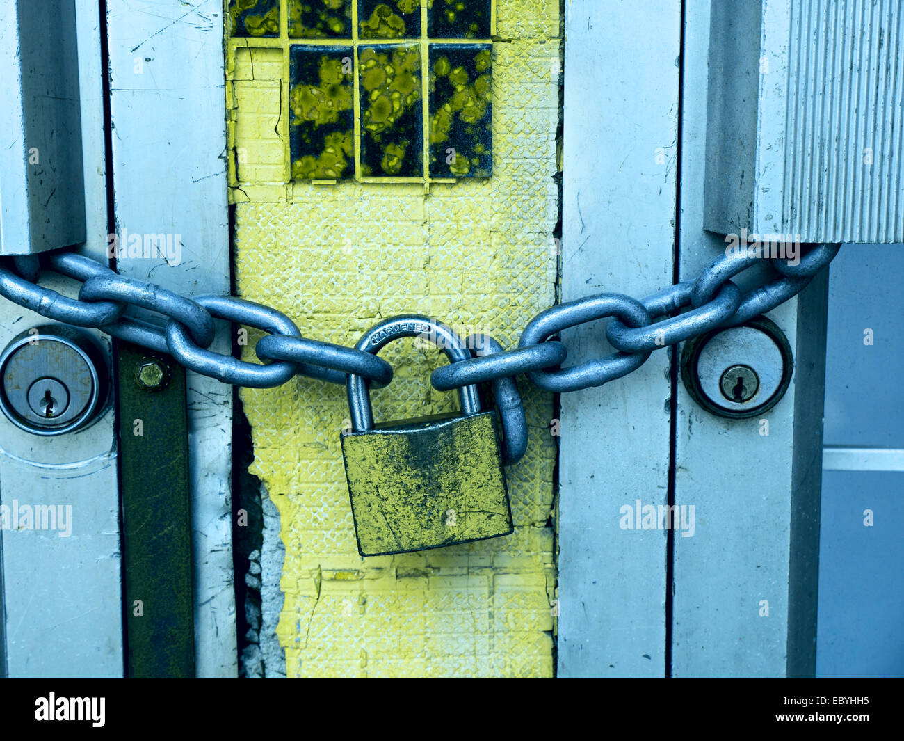 Lock and chain on a commercial buildings metal doors; filtered grunge look - Stock Image