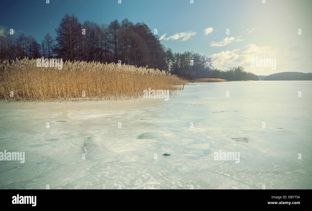 Retro faded and styled picture of a frozen lake. - Stock Image
