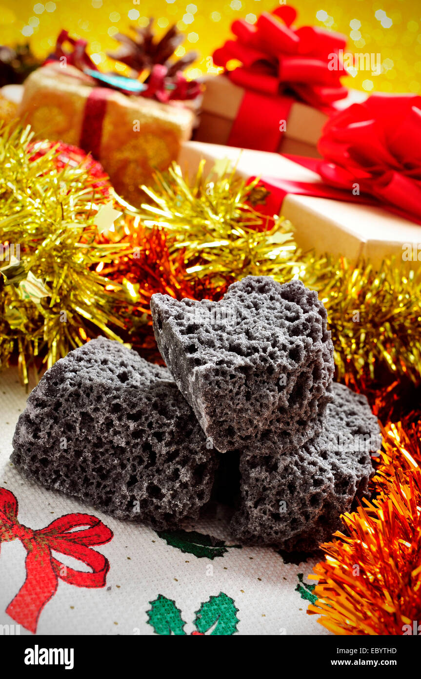 closeup of some lumps of candy coal and some christmas gifts in the background - Stock Image