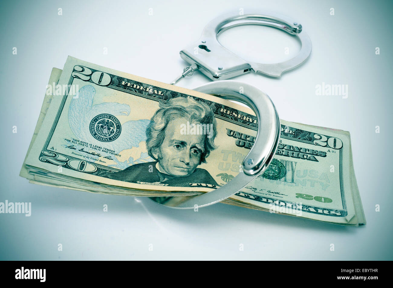 a pair of handcuffs and some dollar bills depicting the idea of arrest for bribery or corruption - Stock Image