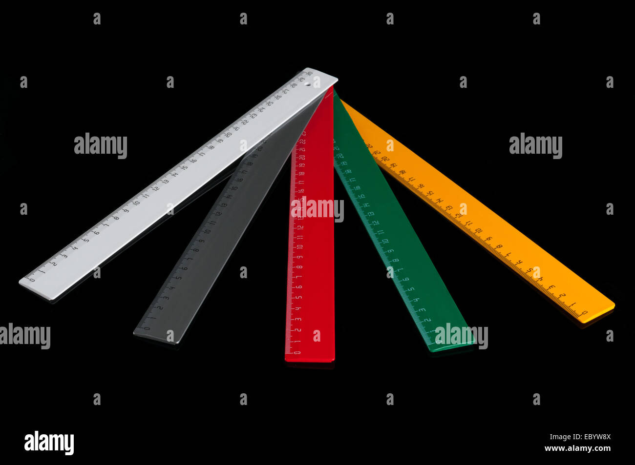 Five colorful rulers isolated on black background - Stock Image
