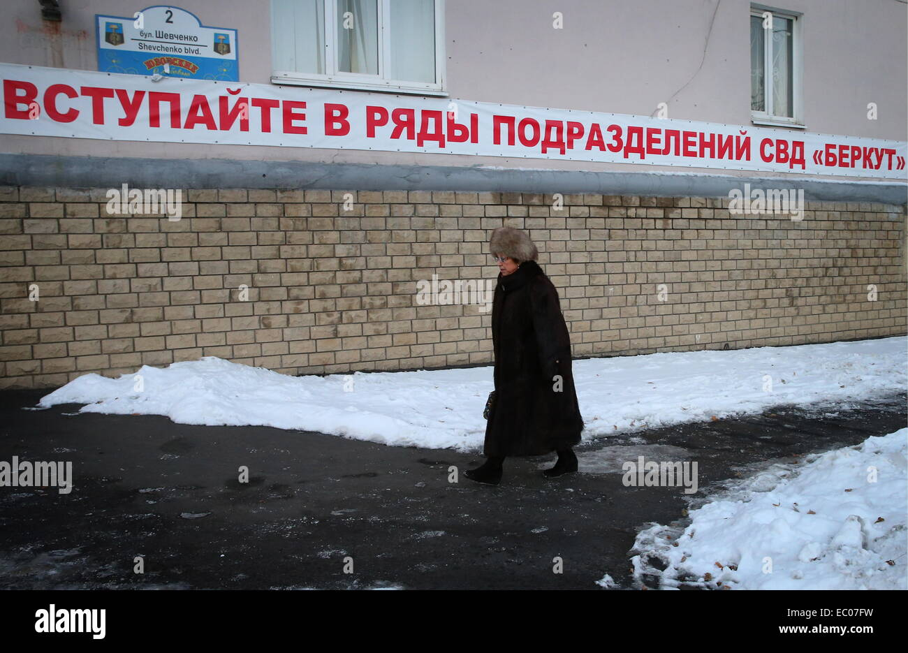 Donetsk, Ukraine. 6th Dec, 2014. Woman walks in a Donetsk street. The slogan calls on citizens to join local police - Stock Image