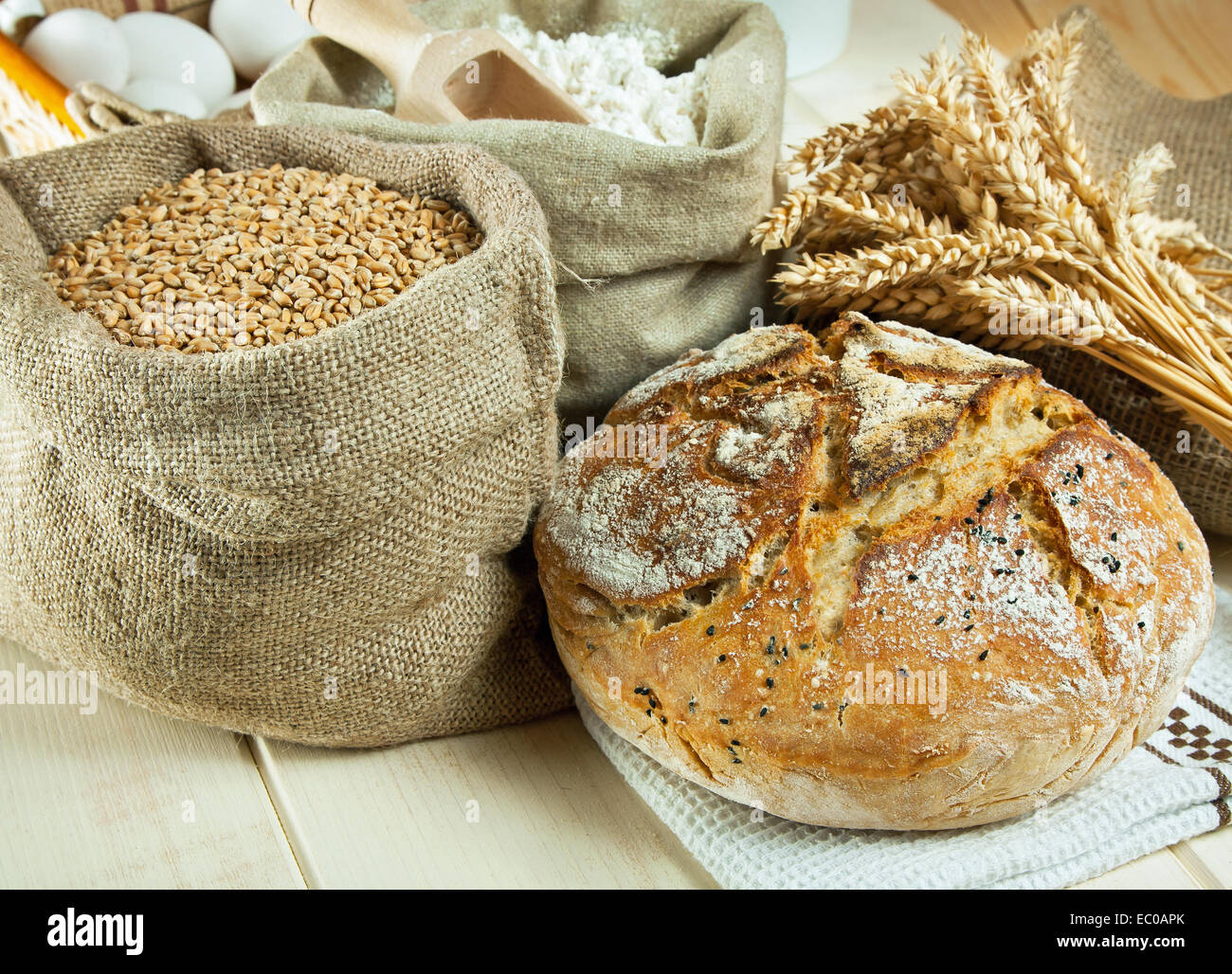Homemade bread and wheat grain on table - Stock Image