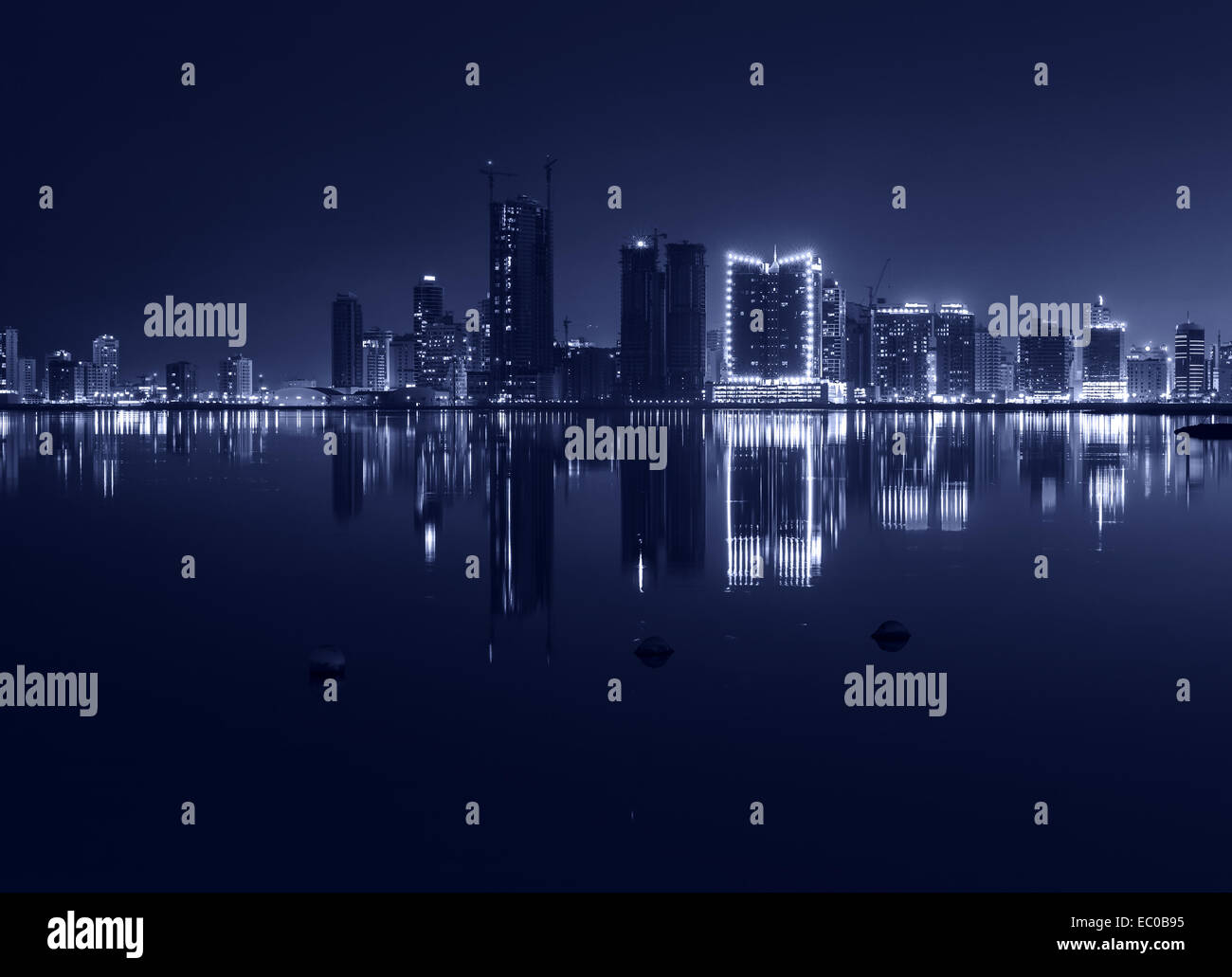 Night modern city skyline with shining lights and reflection in the water. Manama, the Capital of Bahrain, Middle - Stock Image