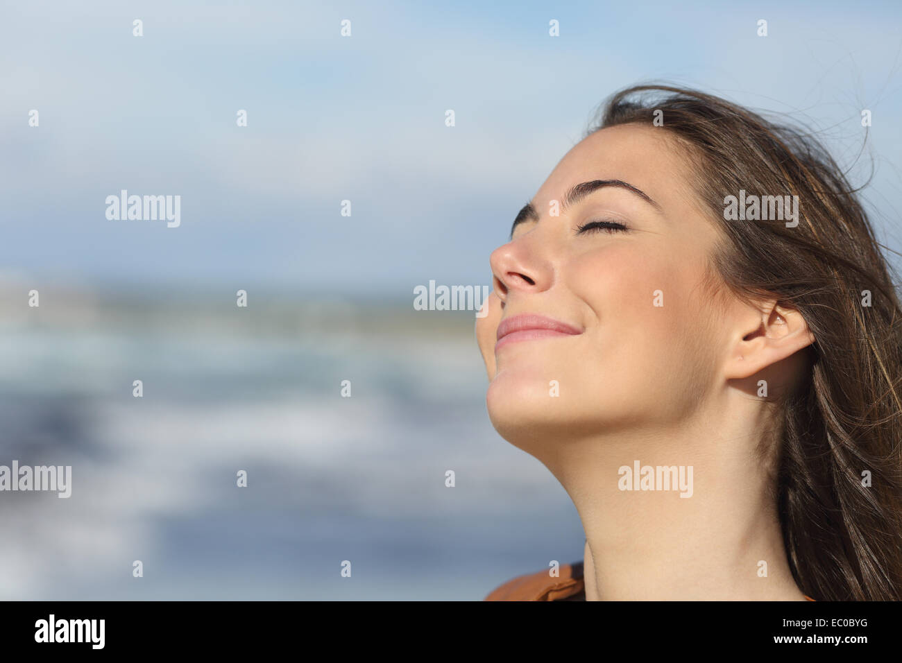 Closeup portrait of a relaxed woman breathing fresh air on the beach - Stock Image