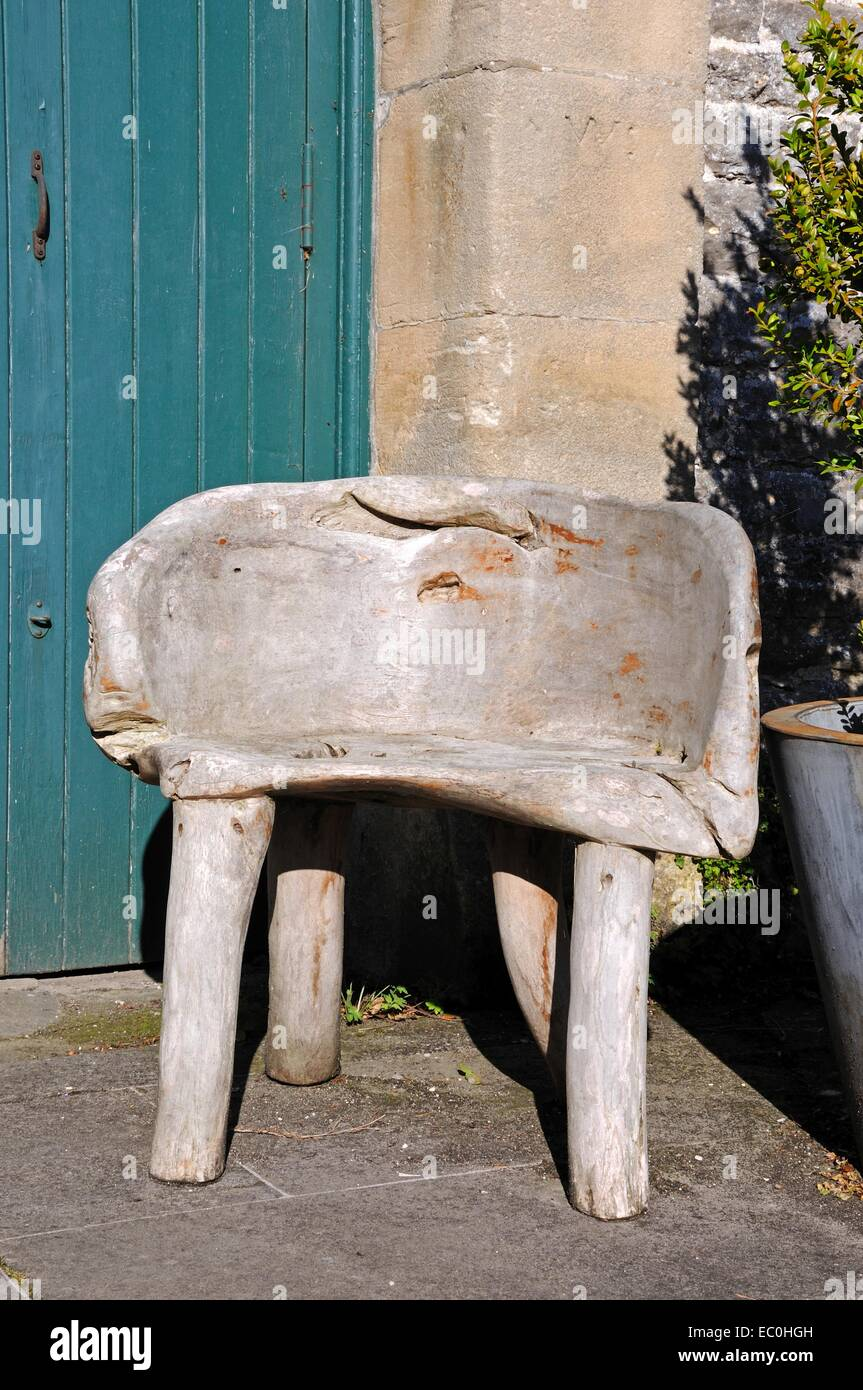 Rustic wooden seat outside the pre-preparatory school building at Tissington Hall, Tissington, Derbyshire, England, Stock Photo