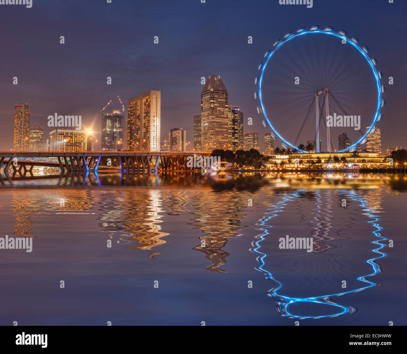 Singapore Flyer and Skyline reflected in the waters of Marina Bay - Stock Image