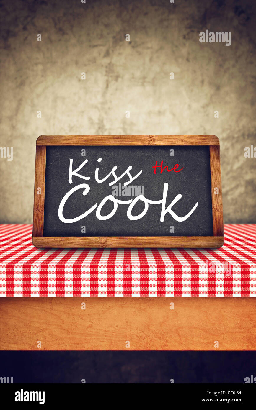 Kiss The Cook Title in white chalk on Restaurant Blackboard. Food and Nutrition background. - Stock Image