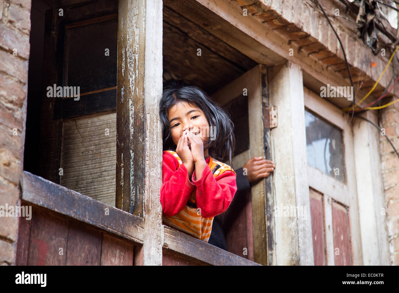 Namaste, young Napali girl in a window in Bhaktapur, Nepal - Stock Image