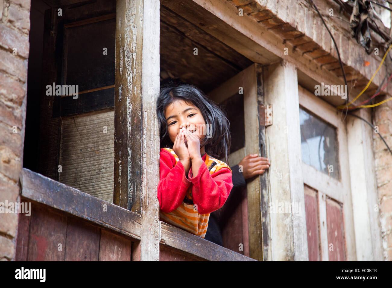 Namaste, young Napali girl in a window in Bhaktapur, Nepal Stock Photo