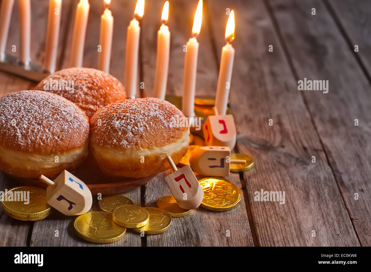 Jewish holiday hannukah symbols - menorah, doughnuts, chockolate coins and wooden dreidels. Copy space background. - Stock Image