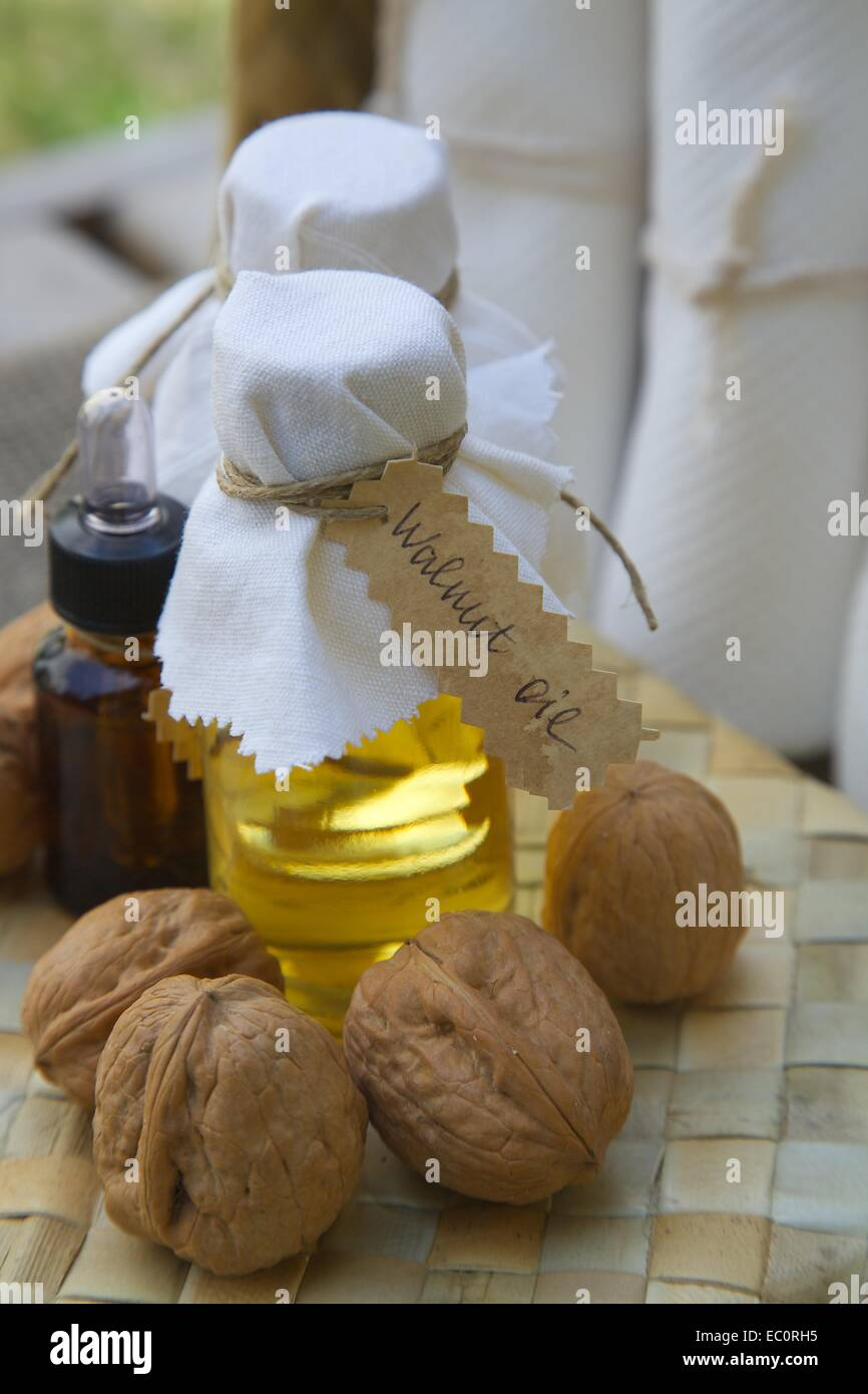 Bottle of walnut oil on the woven surface. Walnuts in the background Stock Photo