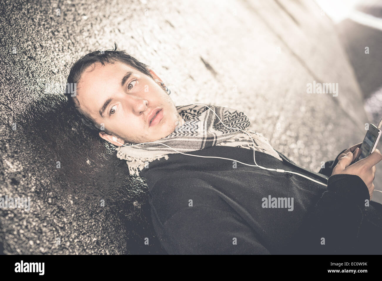Beautifull boy in the sreet with helmets  music of phone - Stock Image