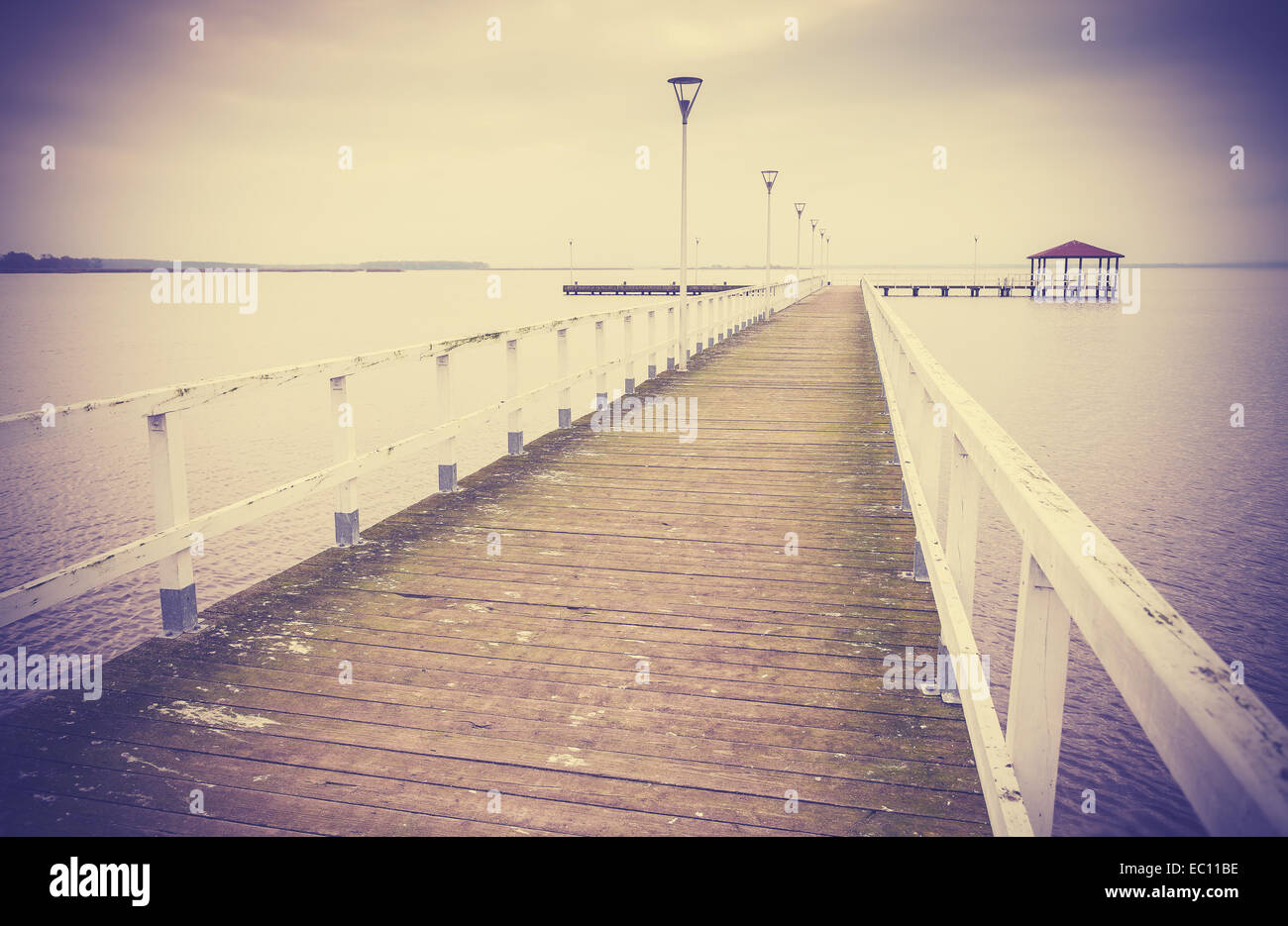 Vintage retro filtered wooden pier at sunset. - Stock Image