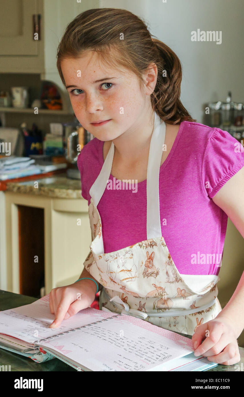 Child (girl) following a recipe whilst cooking or baking in a kitchen - Stock Image