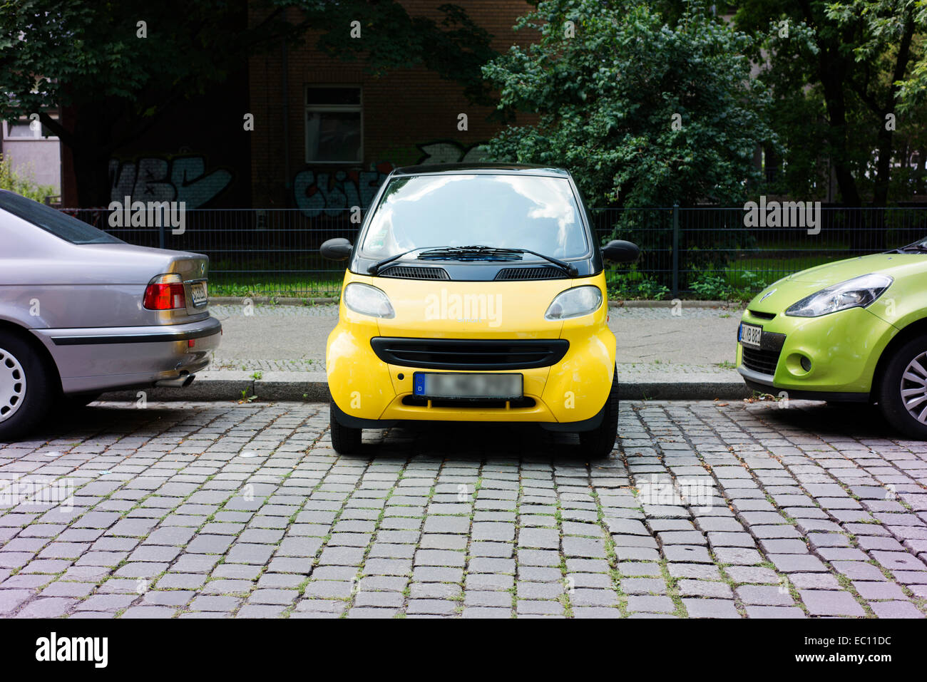 Smart car parked perpendicular from the curb, to save space, in Berlin. - Stock Image