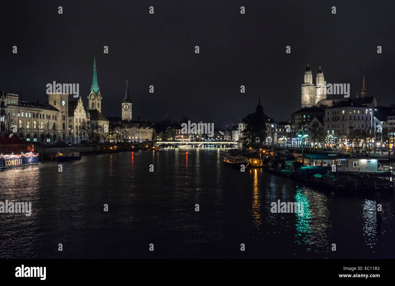 Night view of Zurich's old city, looking down the Limmat river with Grossmunster cathedral (right). - Stock Image