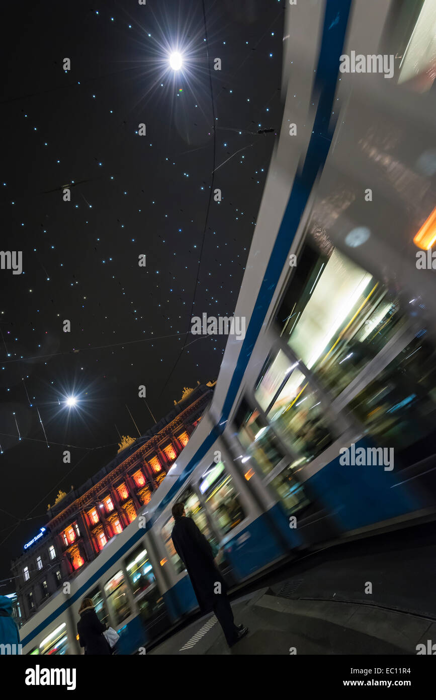 Christmas shoppers around Zurich tramway train on Zurich's Paradeplatz under festive christmas illuminations. - Stock Image