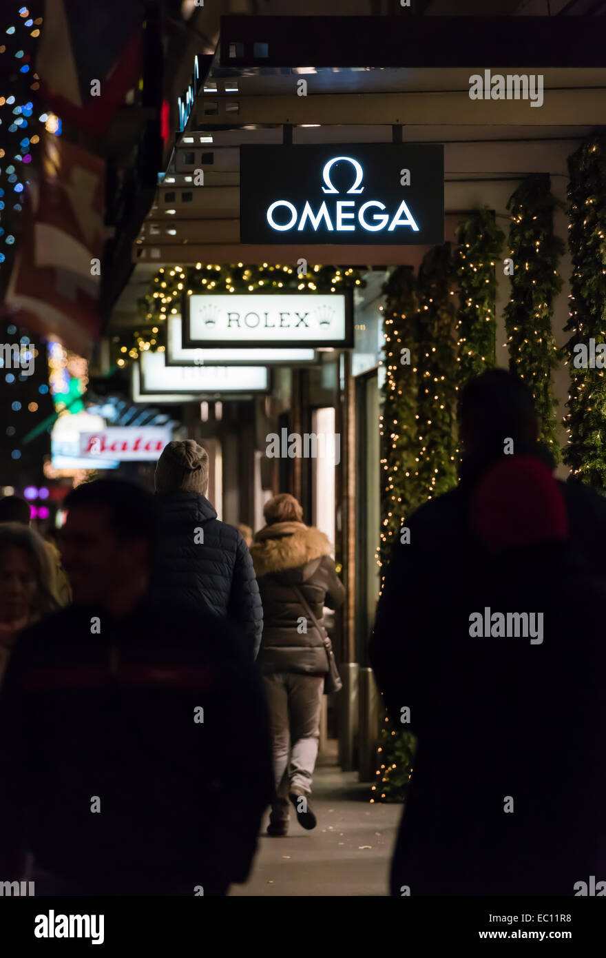 Christmas shoppers at night pass by luxury watch shops on the festively illuminated Zurich (Switzerland)  Bahnhofstrasse. - Stock Image