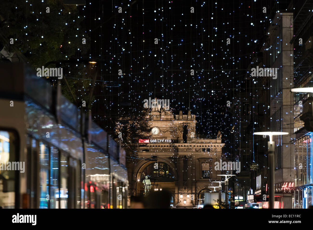 Zurich main station at night, barely visible behind thousands of little lights of the Christmas illumination on - Stock Image