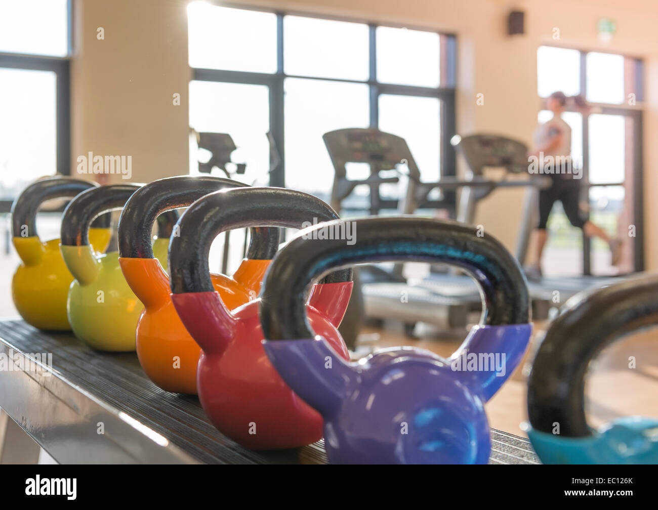 Kettle weights in a gym with a woman on a treadmill in a gym - Stock Image