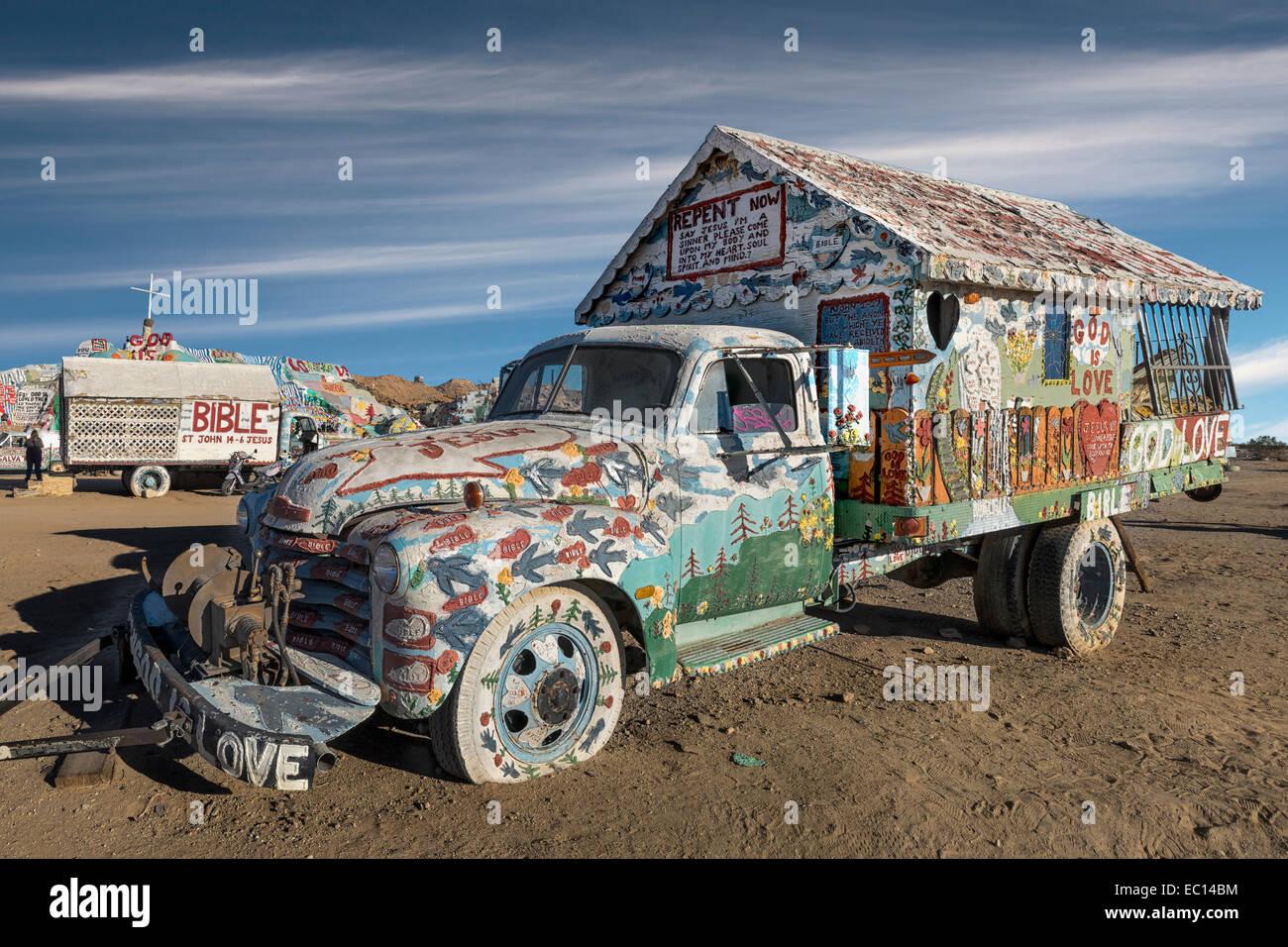 A truck decorated by folk artist Leonard Knight at the Salvation Mountain religious folk art site near Niland California - Stock Image